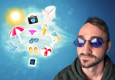 Happy joyful man with sunglasses looking at summer icons Stock Images