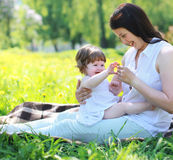 Happy joyful mom and baby playing. In summer park Stock Photos