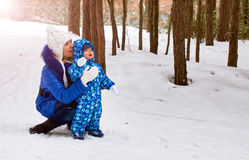 Happy and joyful mother and child on walk, play in the winter forest. Pine forest of Chelyabinsk region, Ural, Russia Royalty Free Stock Photography