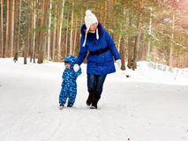 Happy and joyful mother and child on walk, play in the winter forest. Pine forest of Chelyabinsk region, Ural, Russia Stock Photo