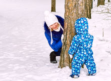 Happy and joyful mother and child on walk, play in the winter forest. Pine forest of Chelyabinsk region, Ural, Russia Royalty Free Stock Photo