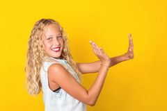 Happy joyful pre-teen girl with perfect smile having fun on yellow background. Attractive lovely pretty winsome sweet cheerful. School girl with wavy blonde royalty free stock photo