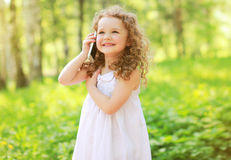 Happy joyful smiling child is speaking on the phone. Outdoors Royalty Free Stock Photo