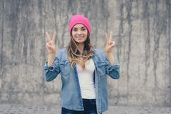 Happy joyful smiling hipster girl in casual clothes and pink hat standing against gray wall and showing victory sign, v-sign, gest stock photos