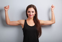 Happy joyful strong young woman showing muscle biceps with smili Stock Photo