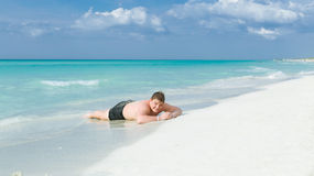 Happy, joyful teenage boy lying on white sand Cuban beach and enjoying his vacation time Royalty Free Stock Photos