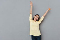 Happy joyful woman with raised hands shouting and having fun Stock Images