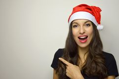 Happy joyful woman with santa claus hat pointing copy space. Christmas girl on gray background. Stock Photography