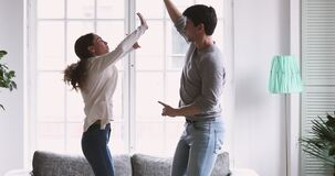 Happy joyful carefree young adult couple dancing in living room