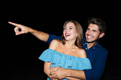 Happy joyful young couple laughing and pointing away. At night royalty free stock images