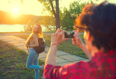 Happy joyful young couple taking photo on smartphone in summer park Stock Photos