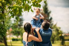 Happy joyful young family father, mother and little daughter having fun outdoors, playing together in summer park royalty free stock photo