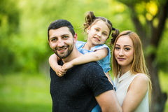 Happy joyful young family father, mother and little daughter having fun outdoors, playing together in summer park, countryside. Royalty Free Stock Images