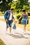 Happy joyful young family father, mother and little daughter having fun outdoors, playing together in summer park stock image