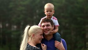 Happy joyful young family father, mother and little son having fun outdoors, playing together in summer park stock footage