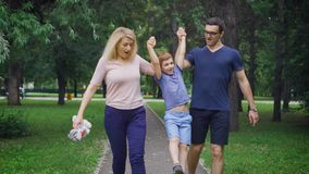Happy joyful young family is having fun outdoors, in summer park. Mom, Dad and kid are laughing and enjoying nature stock footage