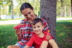 Happy joyful young family while having good time in the park Royalty Free Stock Photos