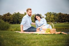 Happy joyful young family husband and his pregnant wife having fun together outdoors, at picnic in summer park stock photo