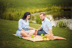 Happy joyful young family husband and his pregnant wife having fun together outdoors, at picnic in summer park royalty free stock photos
