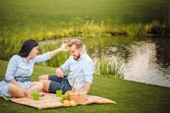 Happy joyful young family husband and his pregnant wife having fun together outdoors, at picnic in summer park royalty free stock photo