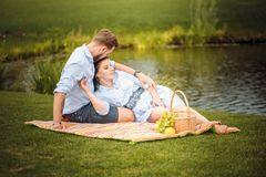 Happy joyful young family husband and his pregnant wife having fun together outdoors, at picnic in summer park stock photos