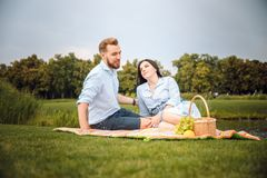 Happy joyful young family husband and his pregnant wife having fun together outdoors, at picnic in summer park royalty free stock photography