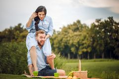 Happy joyful young family husband and his pregnant wife having fun together outdoors, at picnic in summer park stock photography