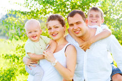 Happy joyful young family in summer park Stock Photo
