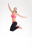Happy joyful young fitness woman jumping. Happy joyful young fitness woman in pink top and black leggings jumping over white background Stock Images