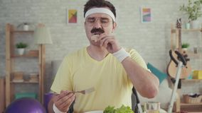 Happy and joyful young sporty man with a mustache eating vegetables sitting at the table stock video footage