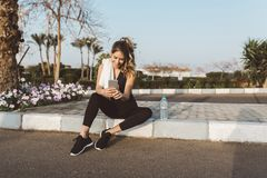 Happy joyful young woman in sportswear sitting outside on street of tropical city. Chatting on phone, expressing. Positivity, true emotions, healthy lifestyle royalty free stock photography