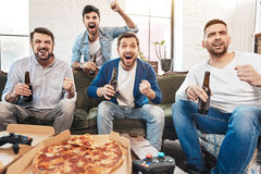 Happy jubilant men expressing their emotions. Absolute happiness. Happy jubilant handsome men holding bottles of beer and expressing their emotions while Stock Photography