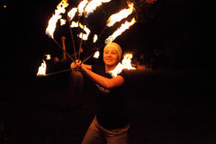 Happy juggler girl playing with fire Stock Photography
