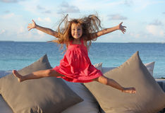 Happy jump. View of a white europian girl child with long blond hair raising up her little hands in the air having great fun by jumping on a sunbed, outdoor in Stock Photography