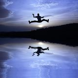 Happy jump. Man jump over a lake...after sunset Royalty Free Stock Photo