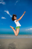 Happy jump at the beach. Young beautiful girl jumping happily at the beach Stock Images