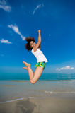 Happy jump at the beach. Young beautiful girl jumping happily at the beach Royalty Free Stock Image