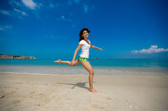 Happy jump at the beach. Young beautiful girl jumping happily at the beach Royalty Free Stock Images