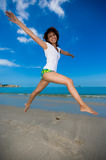 Happy jump at the beach. Young beautiful girl jumping happily at the beach Royalty Free Stock Photography