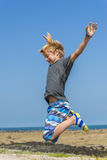 Happy jump. Boy jumping for joy near the sea Royalty Free Stock Photos