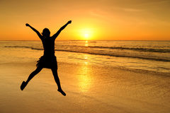 Happy jump woman in Sea Sunset at krabi Thailand Stock Image