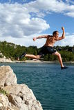 Happy Jumper. A young man jumps from a cliff into the sea Stock Image