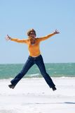Happy jumping. Girl is jumping in the air at a crystal white beach Royalty Free Stock Photo