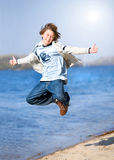Happy jumping boy on beach Stock Image
