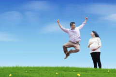 Happy jumping father. A happy young father jumping on the meadow with his pregnant wife Royalty Free Stock Images
