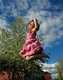 Happy jumping girl. On bird-cherry background Stock Images
