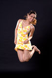 Happy jumping girl. A Happy girl in yellow dress jumping joyfully on a black background Royalty Free Stock Photography