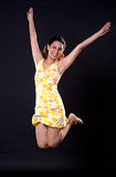 Happy jumping girl. A Happy girl in yellow dress jumping joyfully on a black background Stock Photos