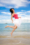 Happy jumping girl. Girl jumping happily by the seashore with the blue sky background Royalty Free Stock Photos