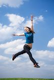 The happy jumping girl. On a background of the blue sky Royalty Free Stock Image